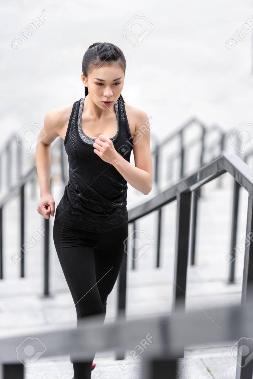 Archivio Fotografico - Donna asiatica in abiti sportivi in   esecuzione su  scale dello stadio 6740673a1d6