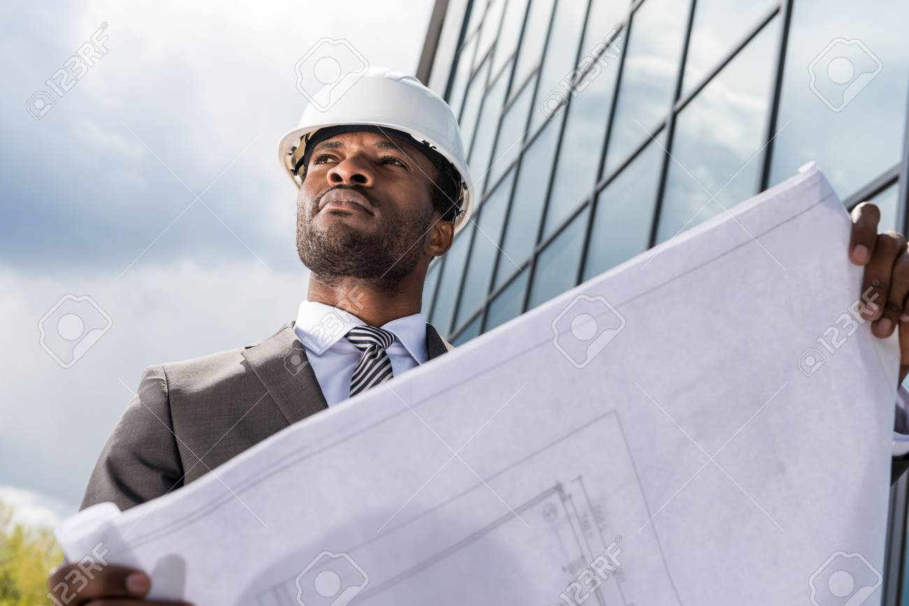 professional architect in hard hat holding blueprint outside modern building - 80149855