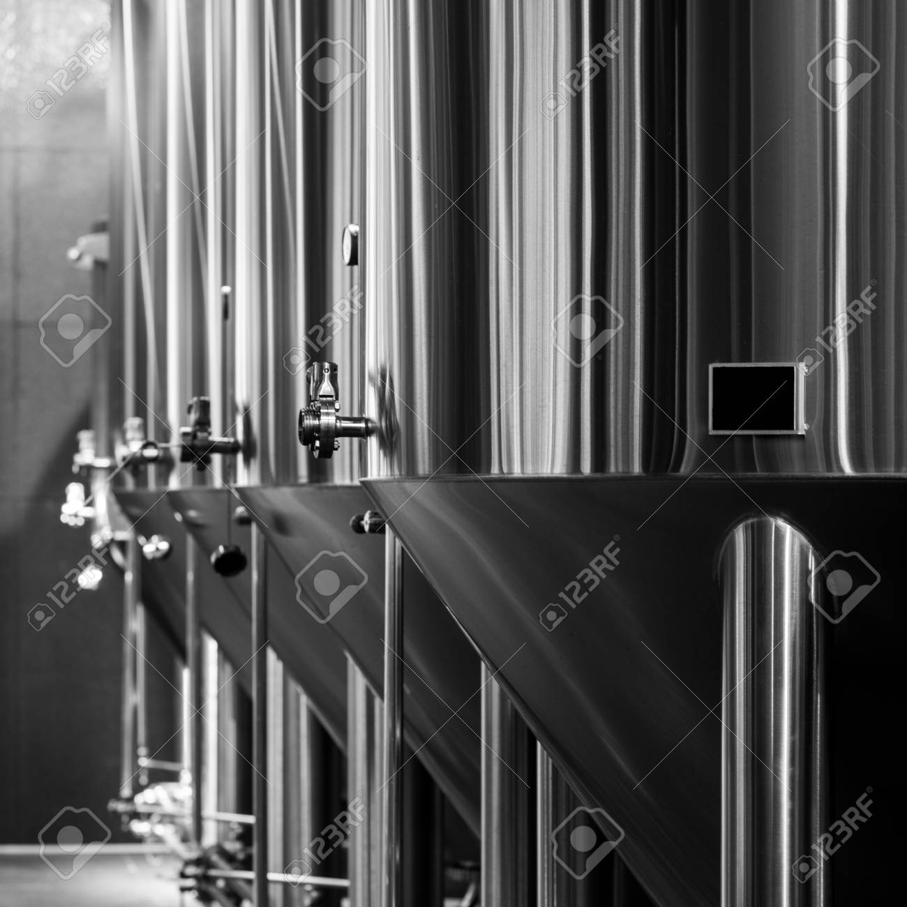 Black and white photo of modern brewery equipment with stainless tanks for the fermentation beer stock