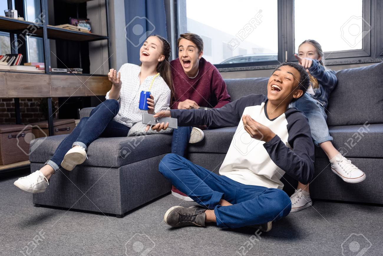 group of teenagers watching movie together at home, teenagers
