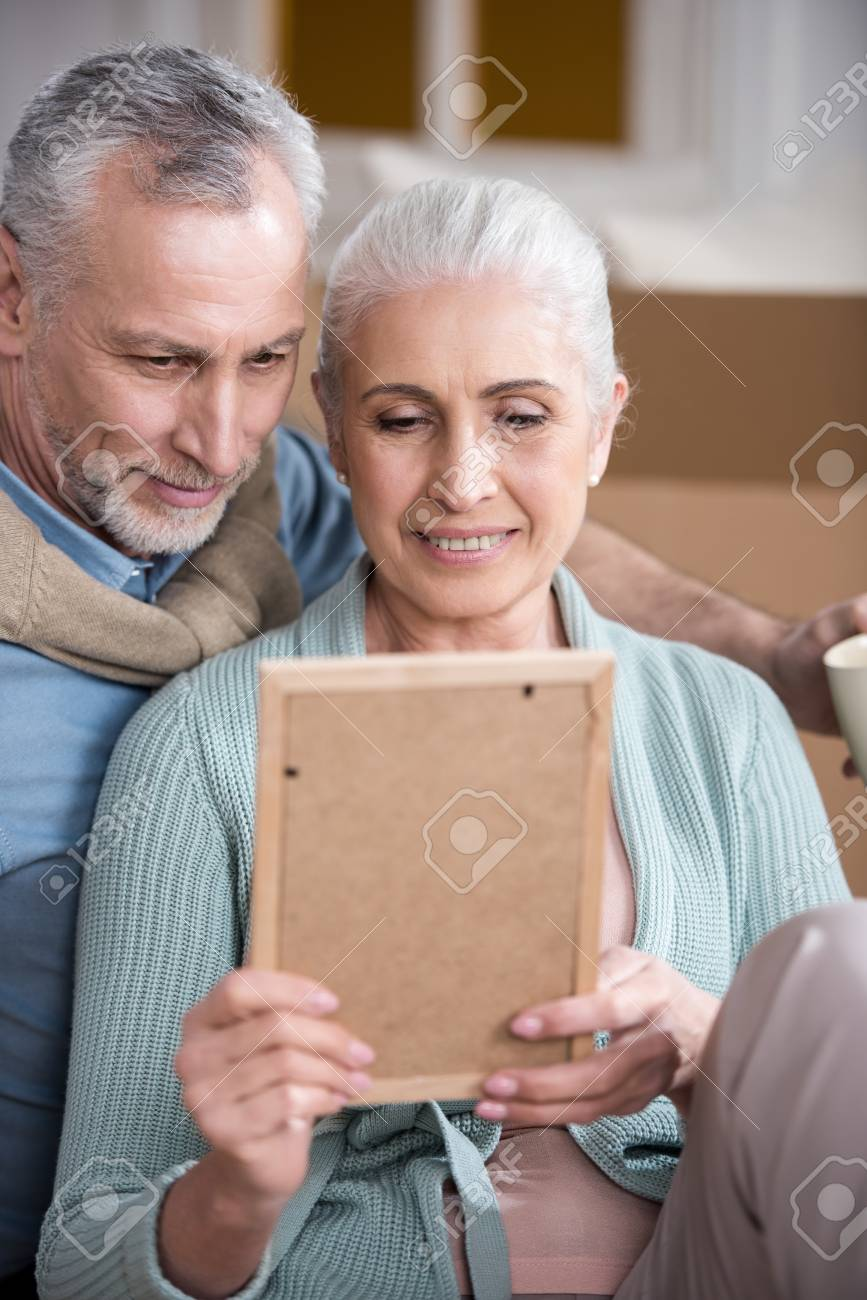 Smiling Husband And Wife Looking At Photo Frame Together Stock Photo