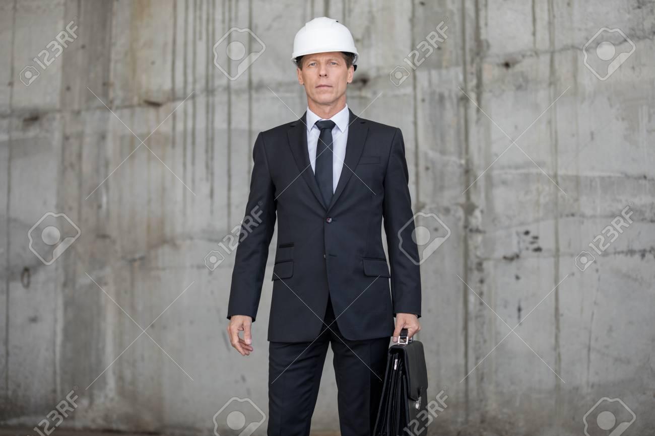 auténtico seleccione para el más nuevo más vendido Arquitecto profesional en casco con maletín y mirando a cámara