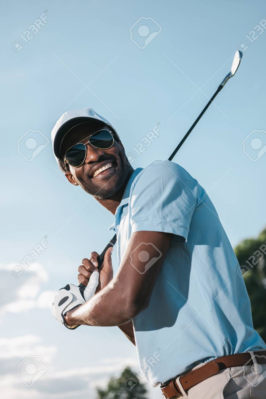 a292b8658ed african american man in cap and sunglasses holding club and playing golf  Stock Photo - 83319062