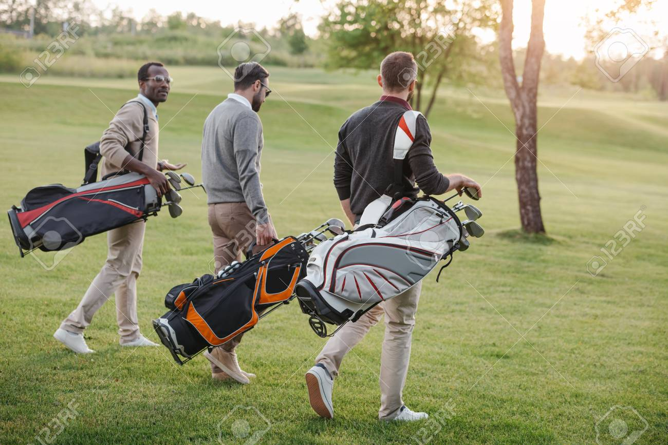 golf players with golf clubs in bags walking on golf course - 83319575