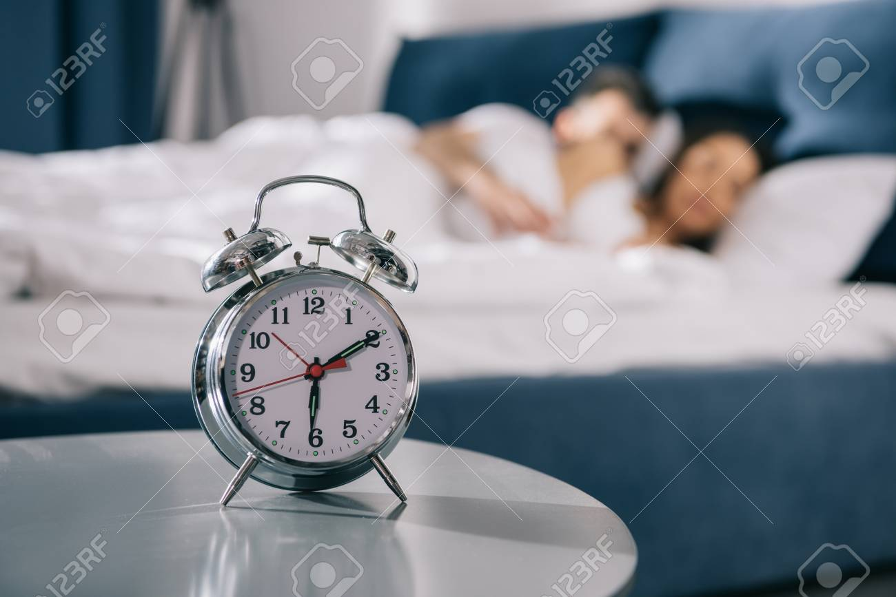 alarm clock standing on table in bedroom at morning