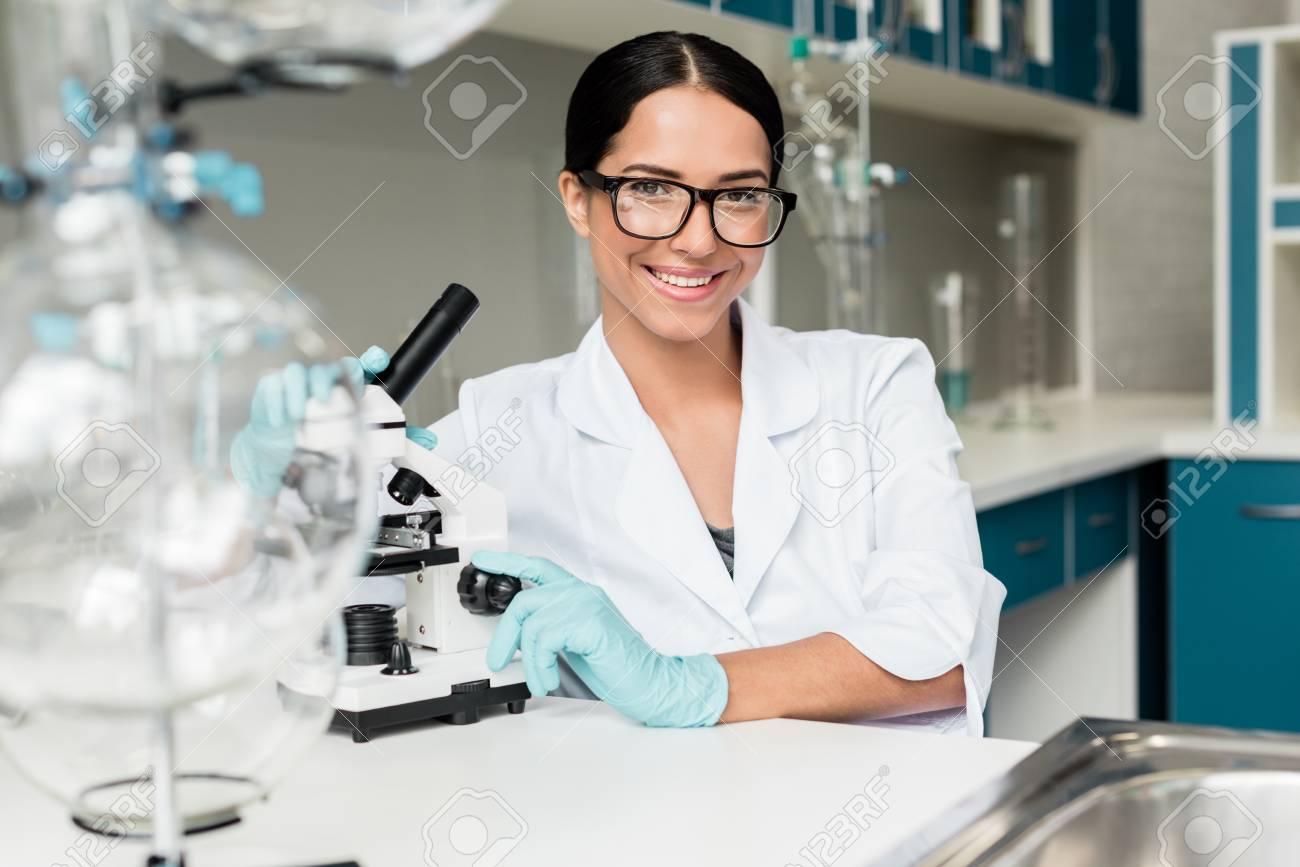 Banque d images - Jeune scientifique à lunettes travaillant avec microscope et  souriant à la caméra dans un laboratoire chimique 831103ee64b1