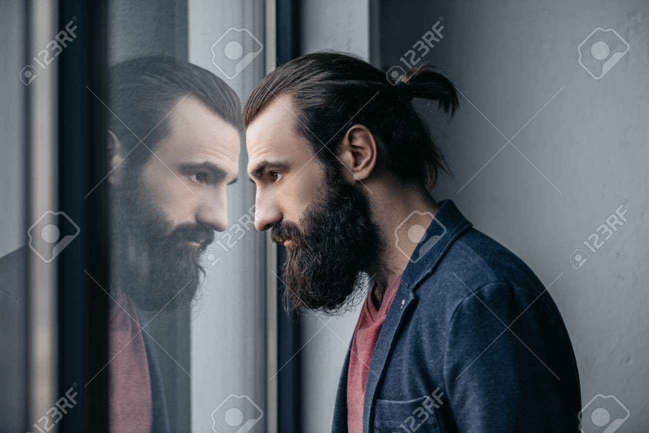 man looking at reflection in glass - 86850082