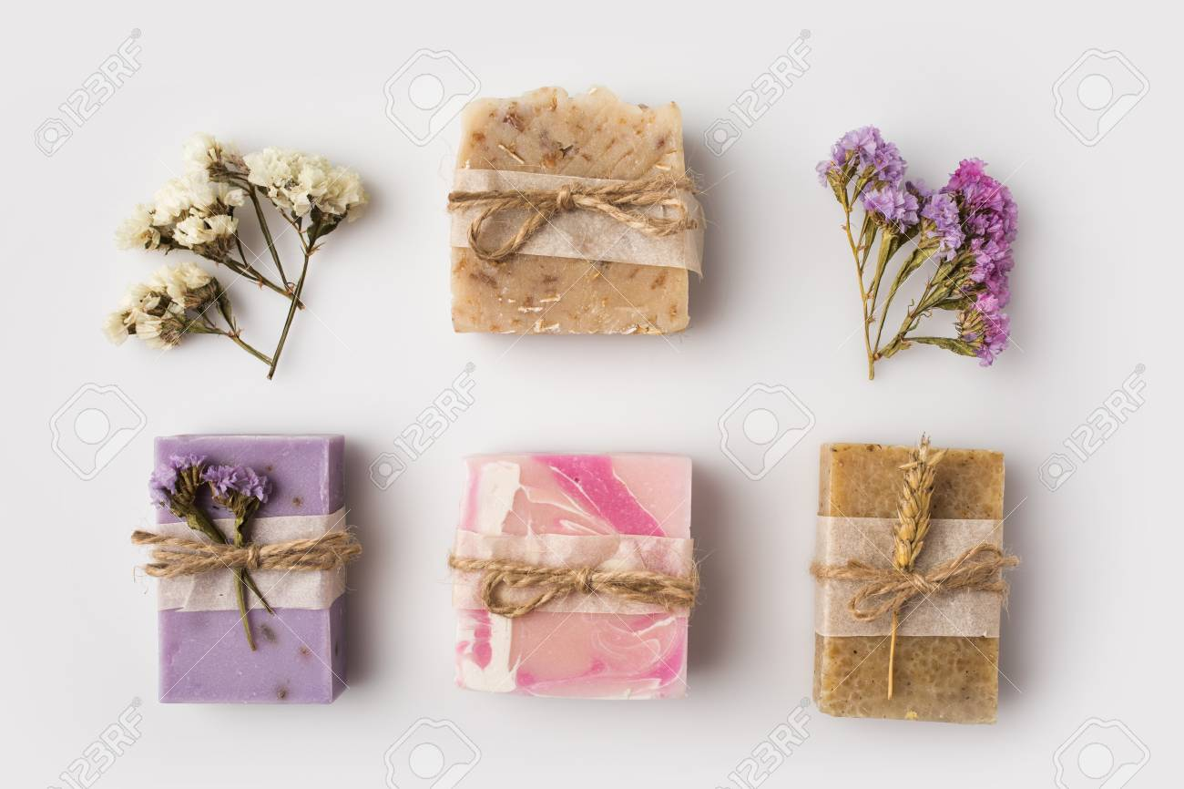 Stock Photo - top view of decorated homemade soap with flowers on white surface
