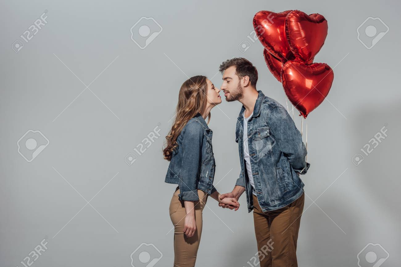 side view of young couple able to kiss while man holding red heart shaped balloons - 93620761