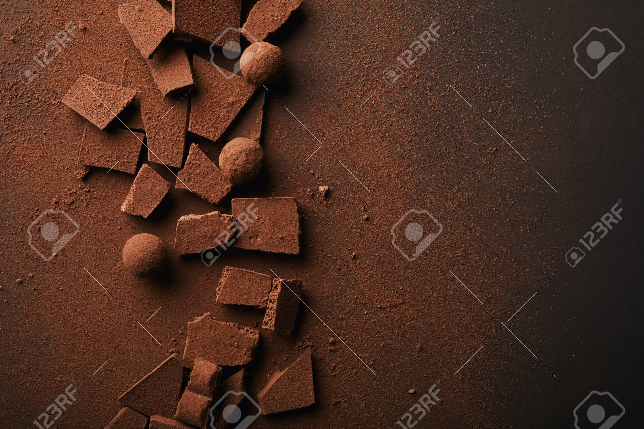 flat lay with arranged truffles and chocolate bars with cocoa powder on tabletop - 93896291