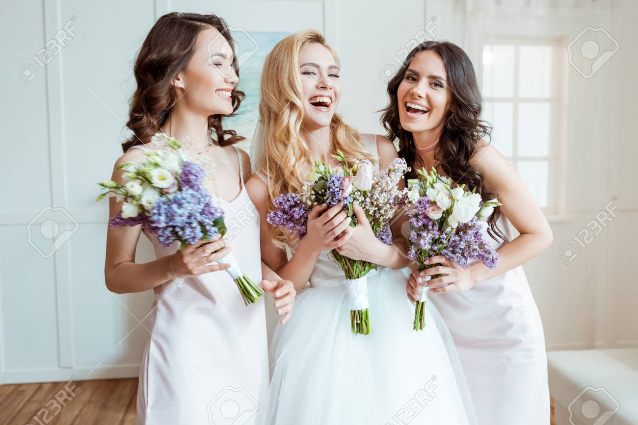laughing bride with bridesmaids - 94853044
