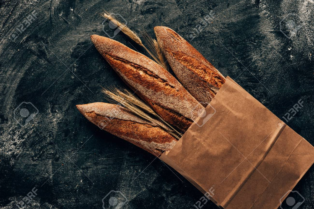 top view of arranged french baguettes in paper bag and wheat on dark tabletop with flour - 97453430