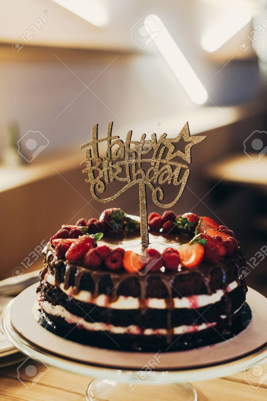 Happy Birthday Sign On Chocolate Cake With Fruits Stock Photo