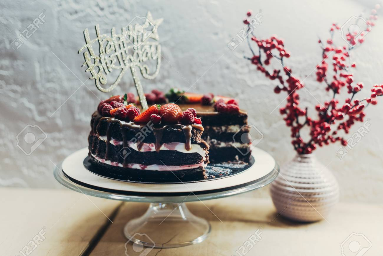 Cake With Happy Birthday Sign On Stand And Vase Berries A Table Stock