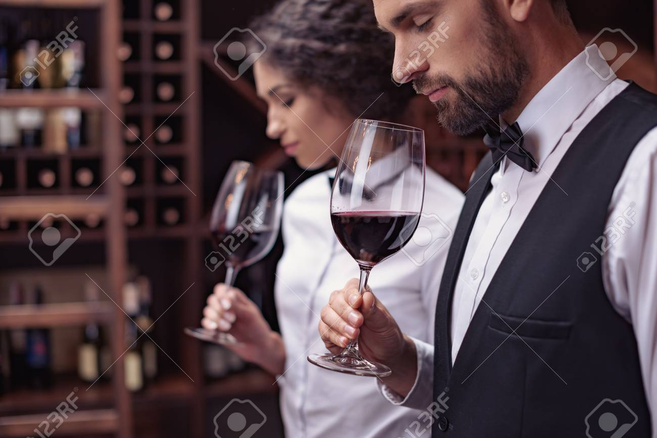 Two sommeliers, male and female tasting red wine in cellar - 102353938