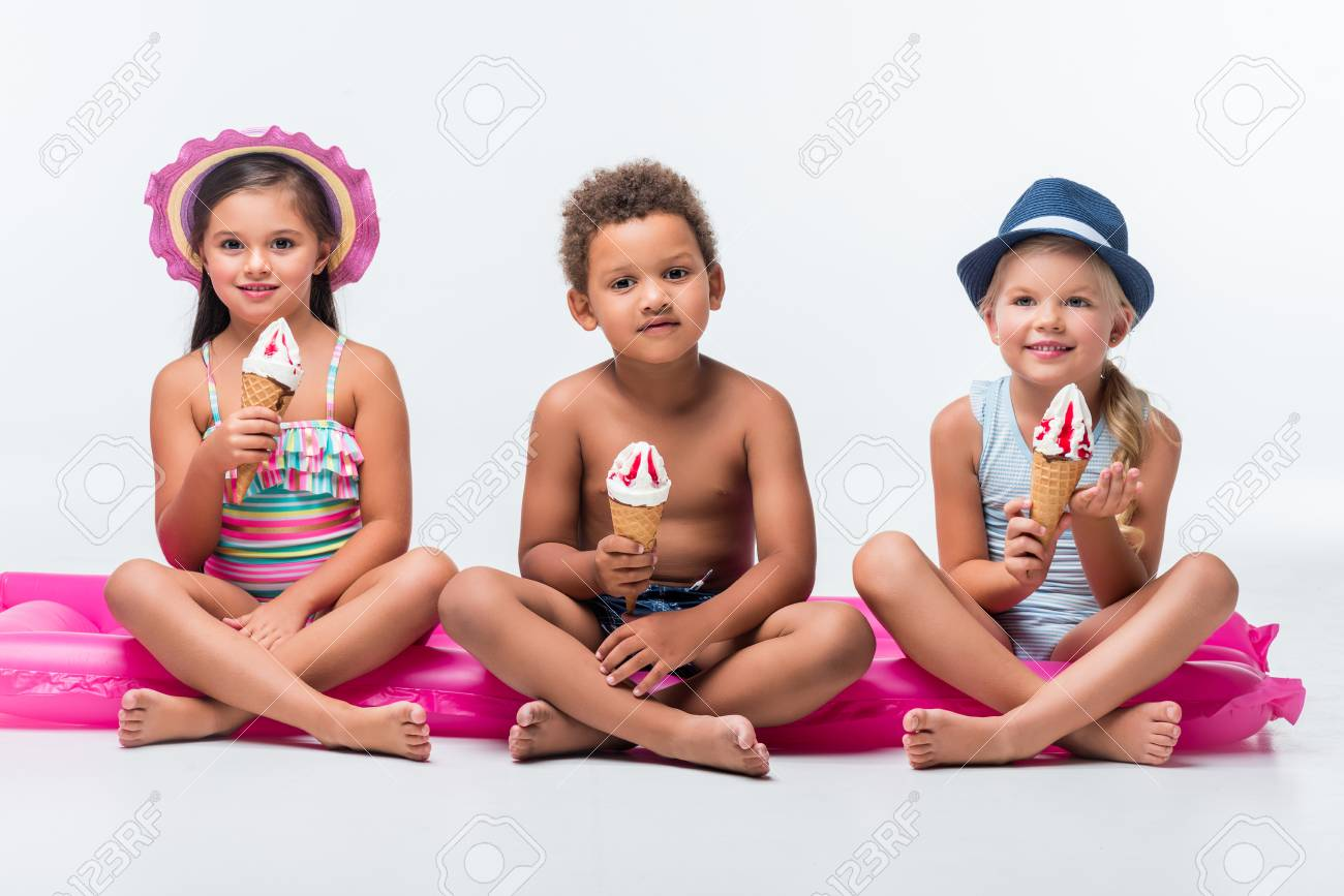 11f6436662fe4 adorable multiethnic kids in swimwear eating ice cream while sitting on  swimming mattress Stock Photo -