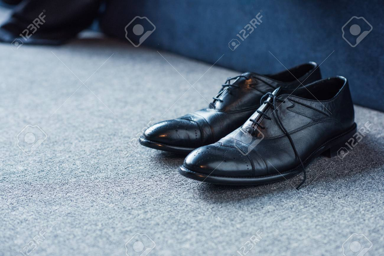Black male leather shoes placed on carpet floor - 102296406