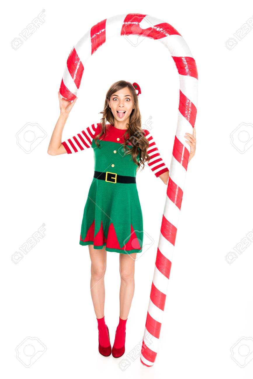 Christmas Elf Costume.Grimace Woman In Elf Costume Holding Decorative Christmas Lollipop