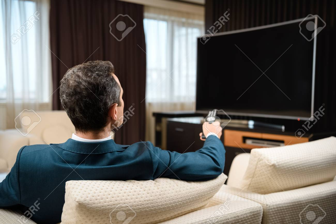 Businessman in formal suit sitting on sofa in hotel room and watching television - 102318792