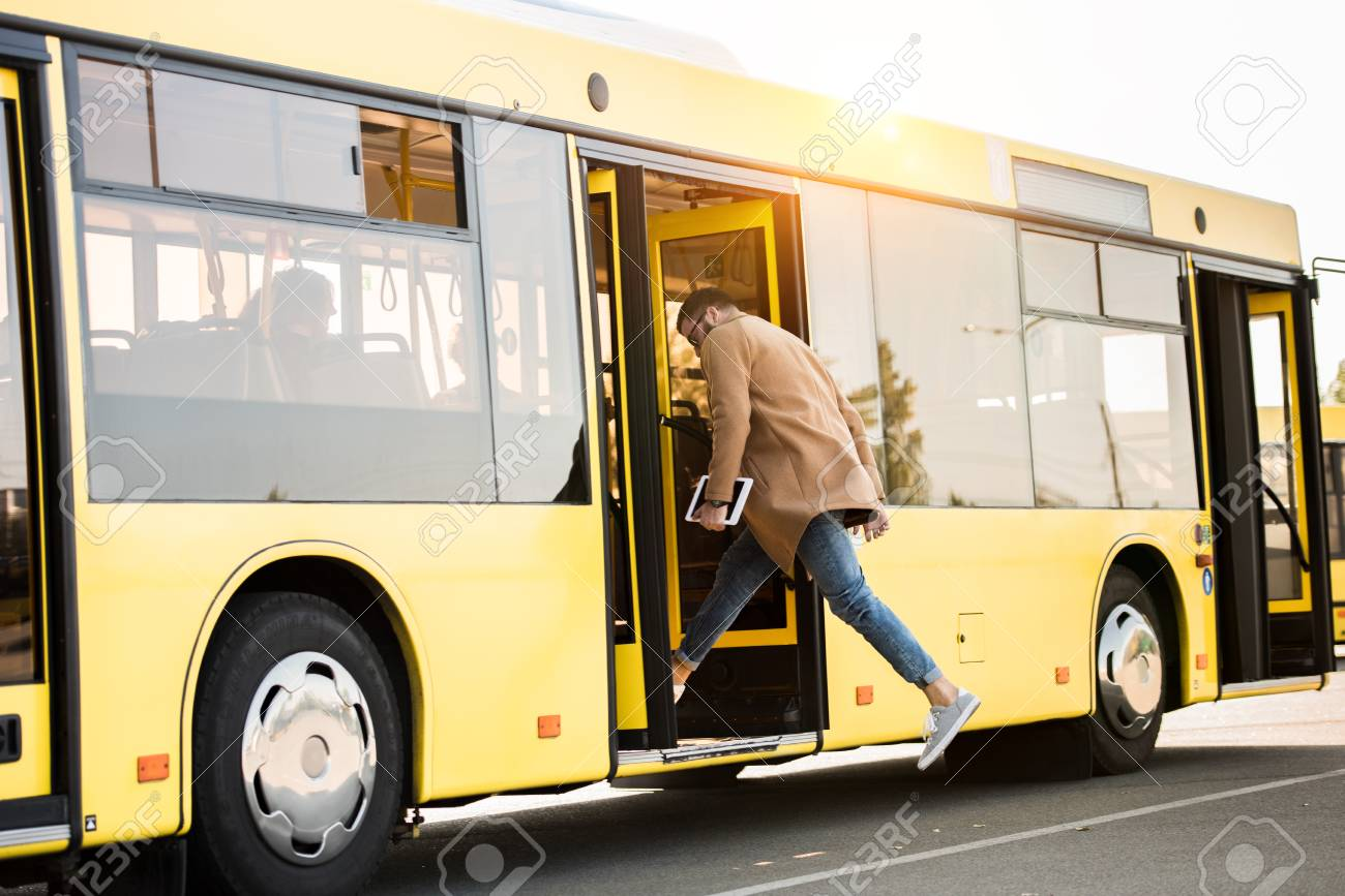 full length view of young man holding digital tablet and entering bus - 102323215