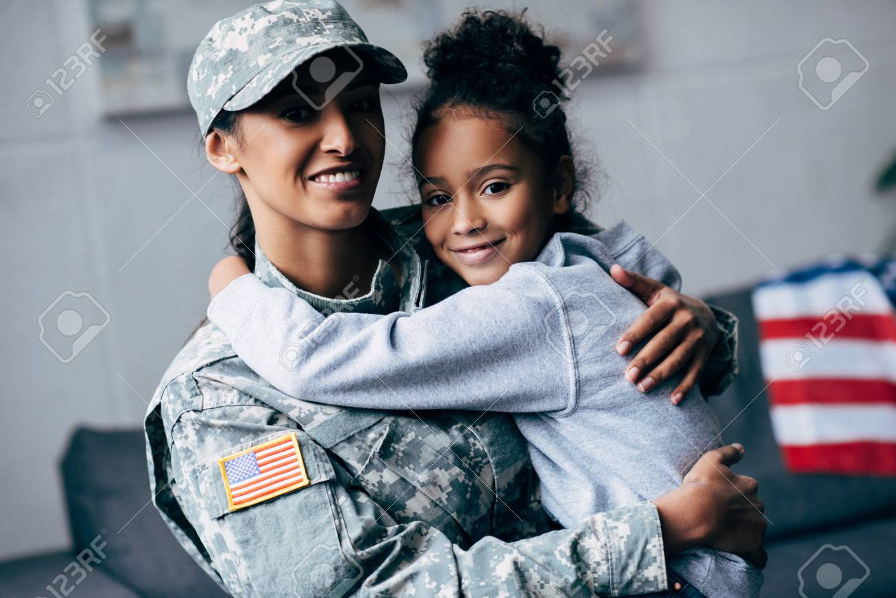 smiling african american daughter hugging mother in military uniform at home - 102611958