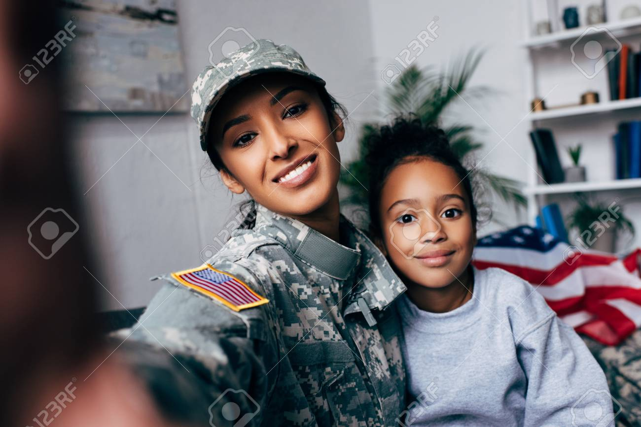 smiling african american daughter and soldier in military uniform taking selfie at home - 102611965