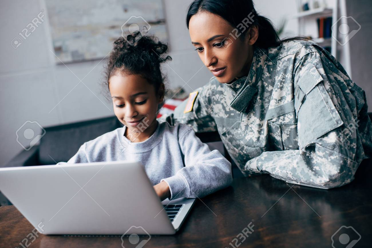 african american mother in military uniform and daughter using laptop at home - 102611431