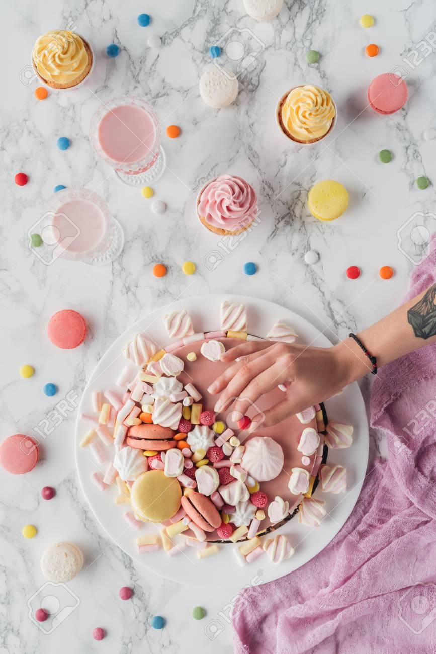 Cropped View Of Woman Putting Little Candy On Pink Birthday Cake Standard Bild