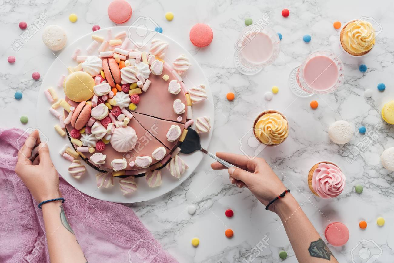 Cropped View Of Woman Taking Piece Pink Birthday Cake With Marshmallows And Macarons Standard