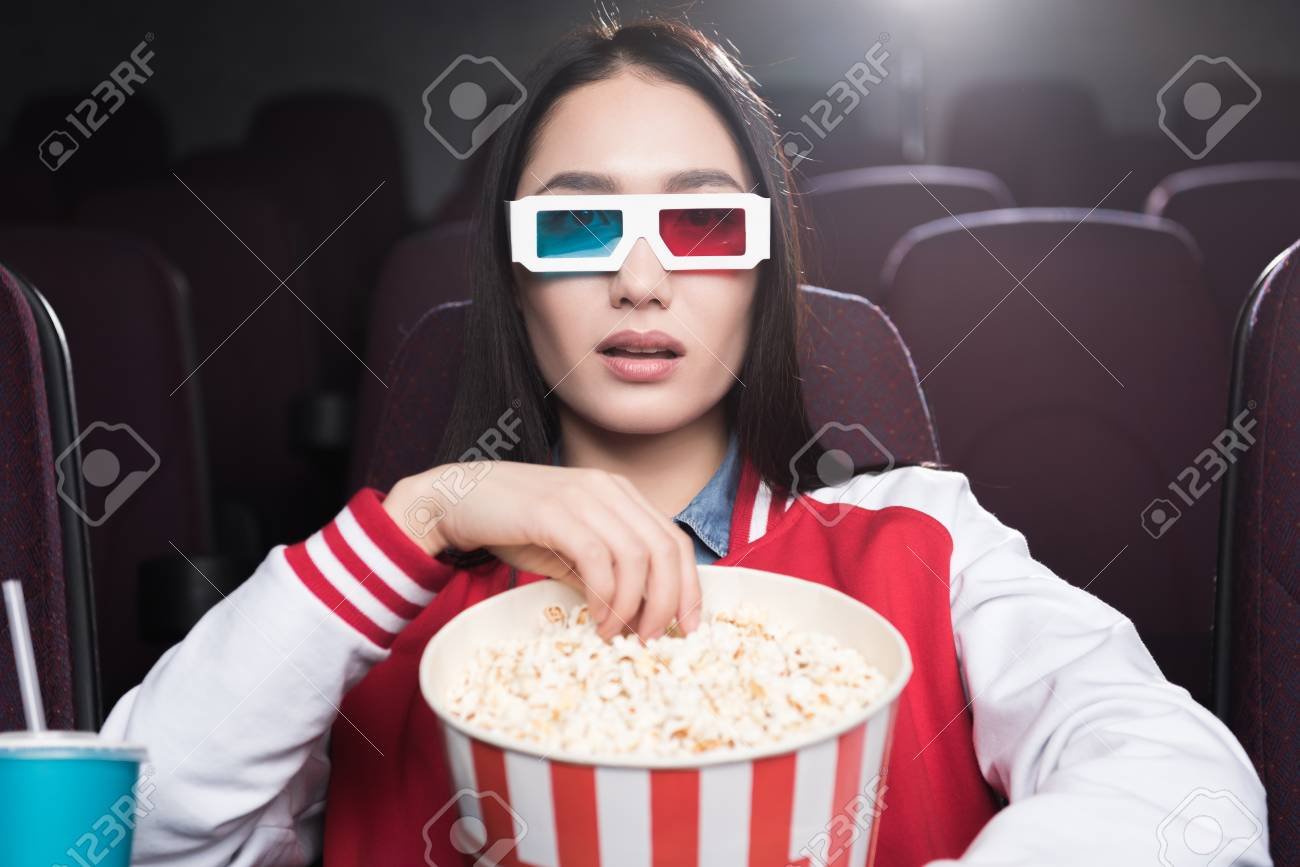 3D Asian Girl young asian girl in 3d glasses with big basket of popcorn watching..