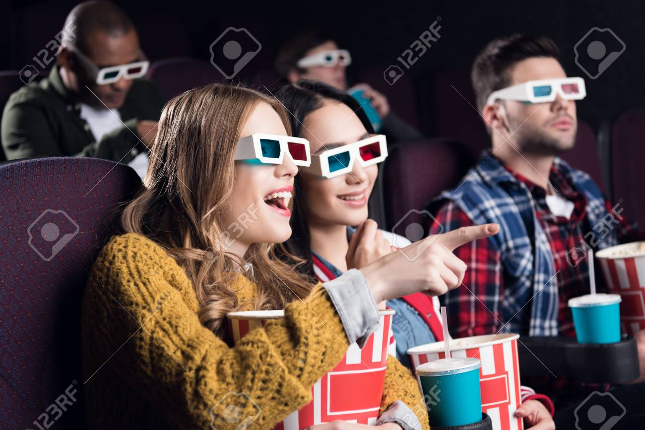 young smiling friends in 3d glasses with popcorn watching film