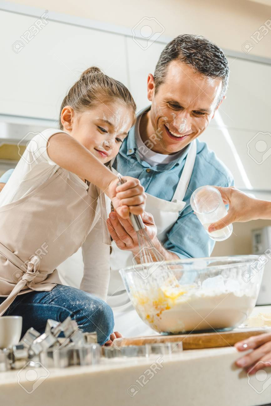 happy family, little kid with father mixing dough in bowl by hands at kitchen - 104664355