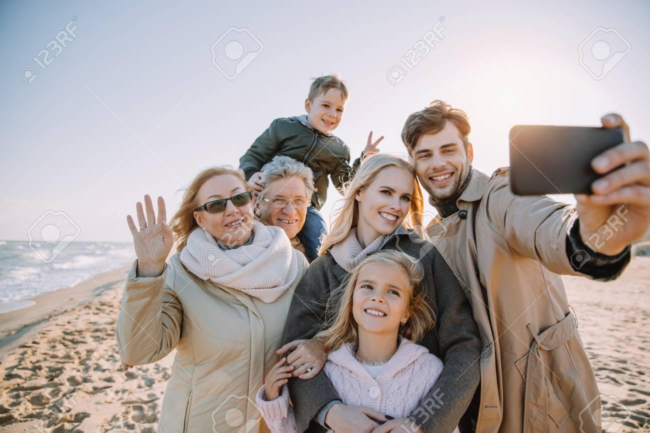 multigenerational family taking selfie on smartphone at seaside - 104550952