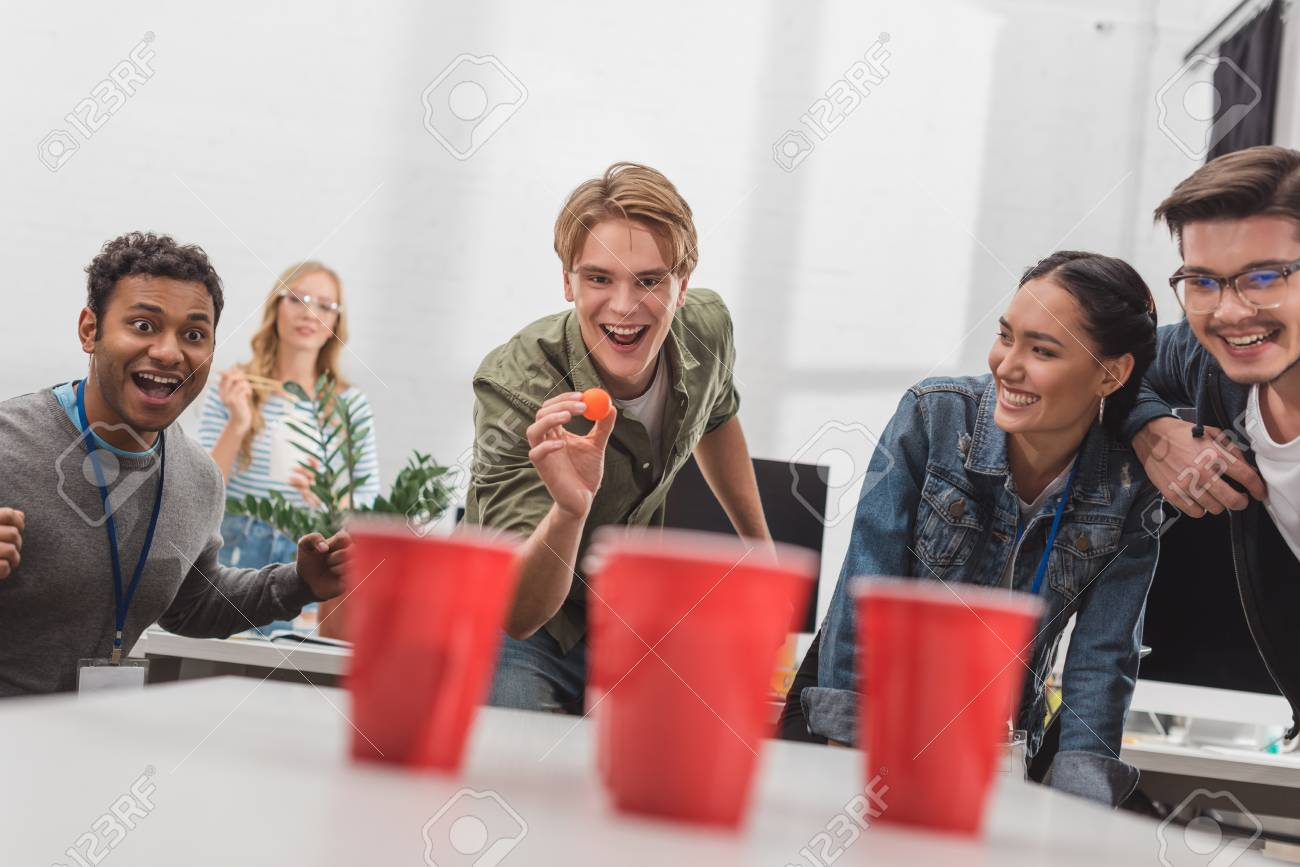 young attractive people playing beer pong at modern office after work - 104557051