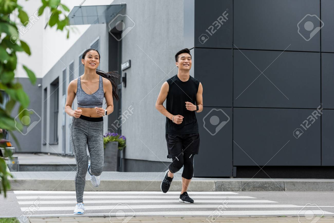 smiling asian sportsman and sportswoman running at city street - 105674928