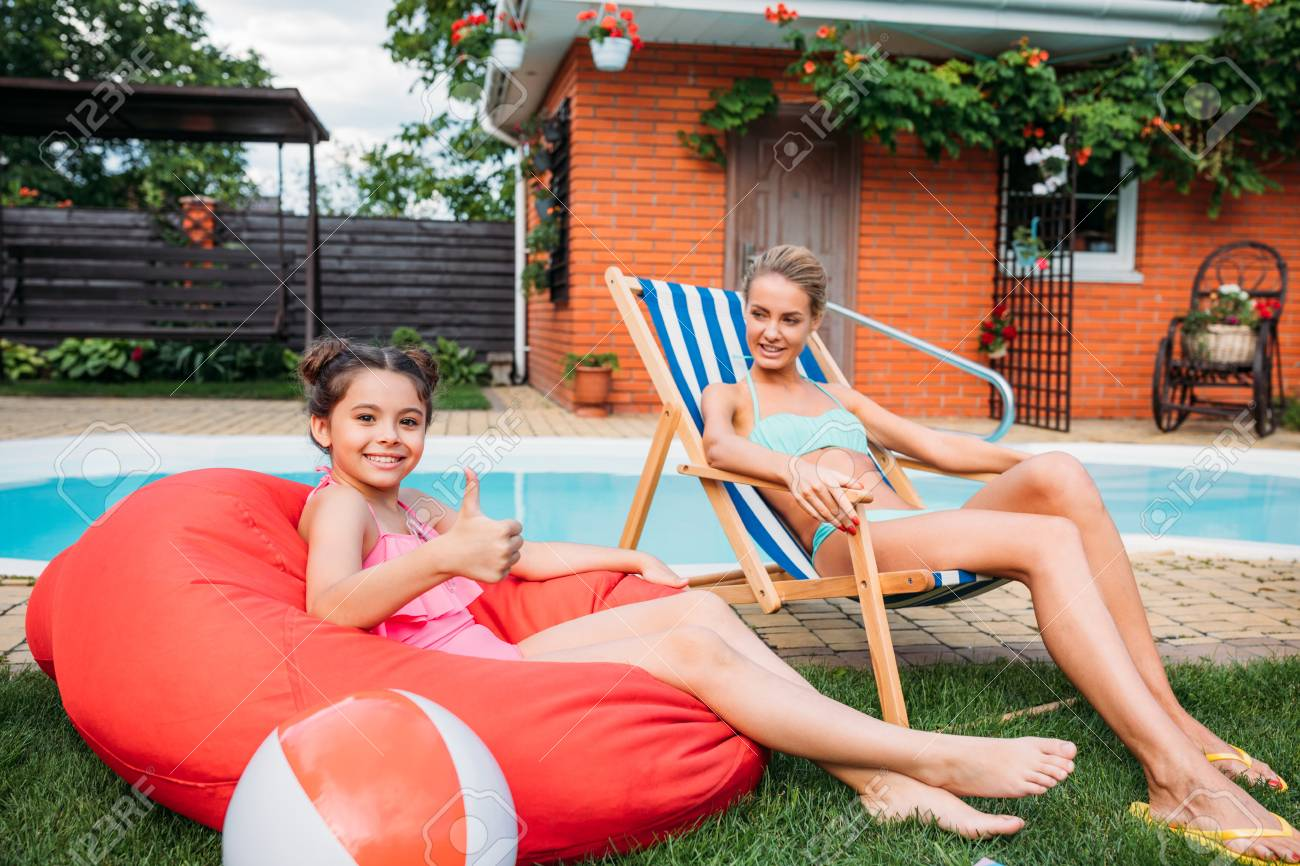 mother and smiling daughter resting near swimming pool on backyard on summer day - 106105221