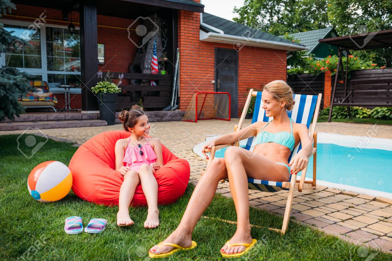 mother and smiling daughter resting near swimming pool on backyard on summer day - 106486568