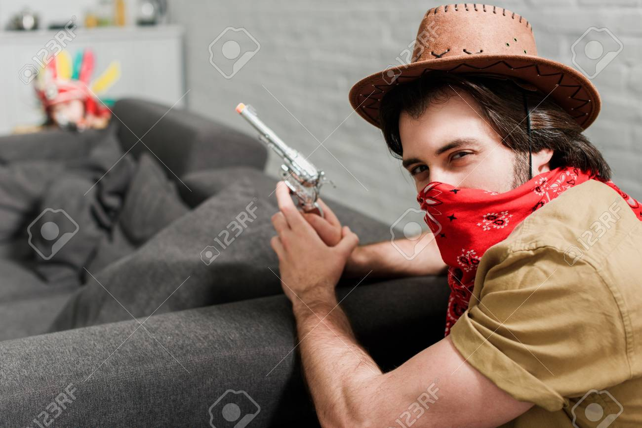 side view of man in red bandana and cowboy hat with toy gun at sofa at 5b64241e4fc