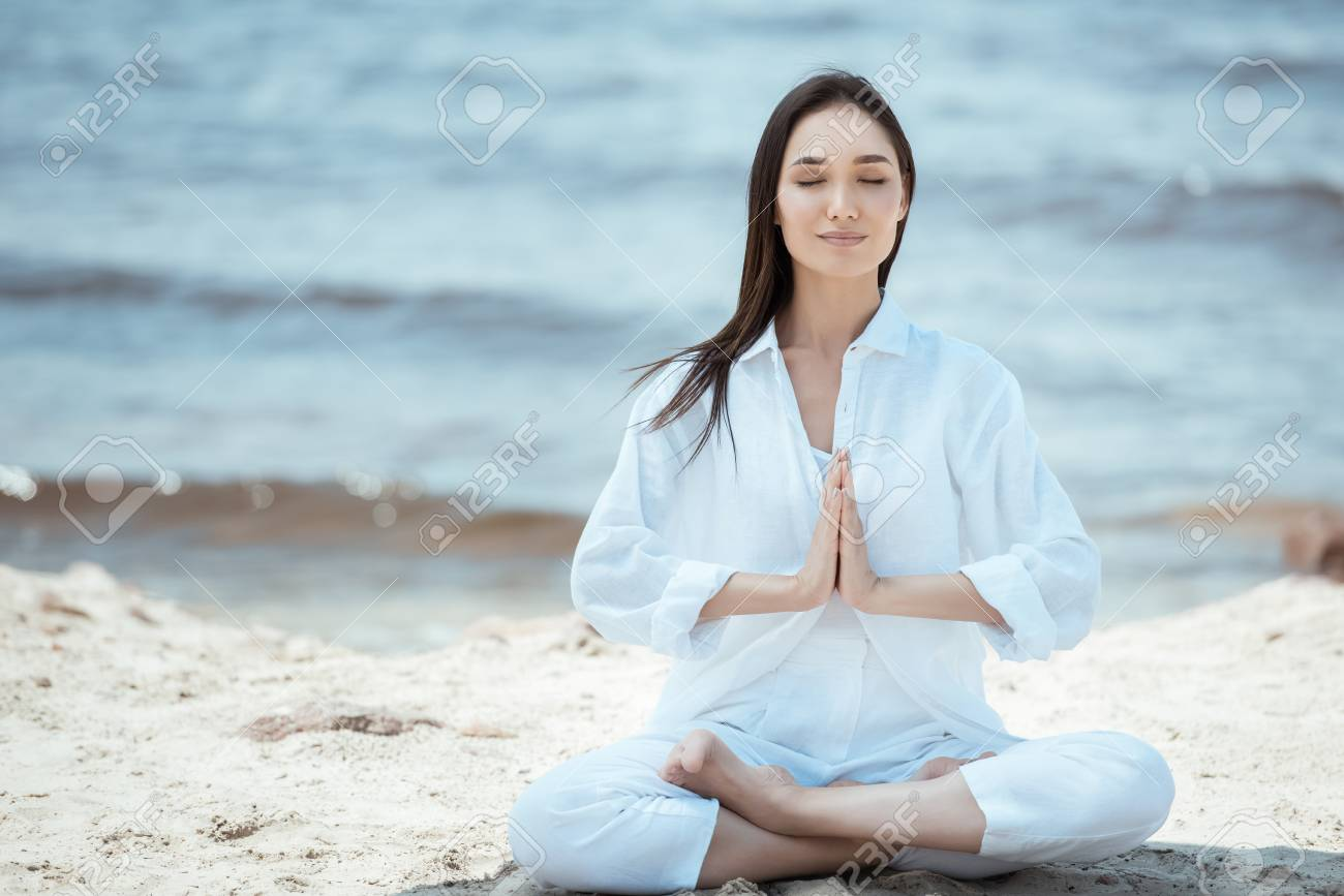 concentrated young asian woman in anjali mudra (salutation seal) pose on beach - 106049312