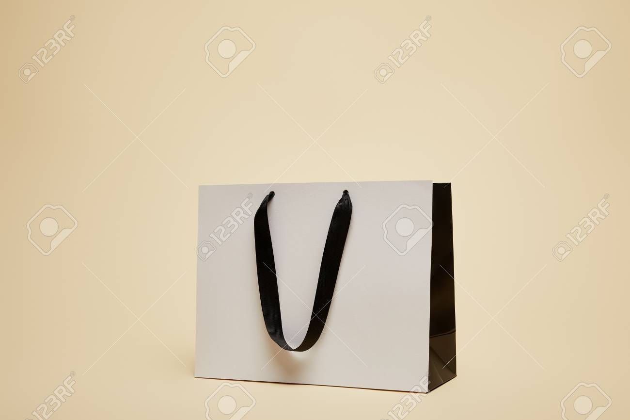 one white shopping bag isolated on beige - 106685297
