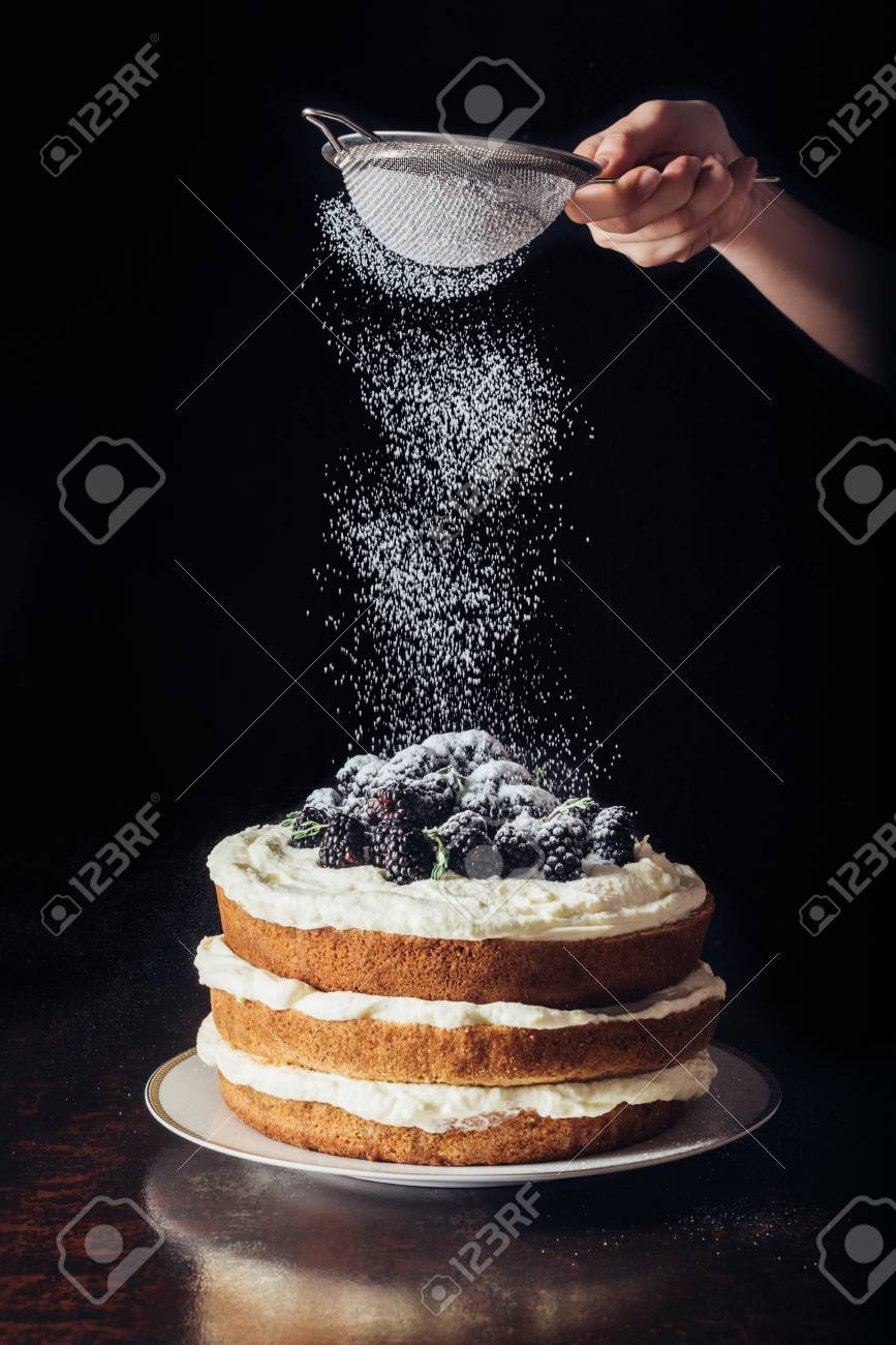 cropped shot of woman spilling sugar powder onto delicious blackberry on black - 106420426