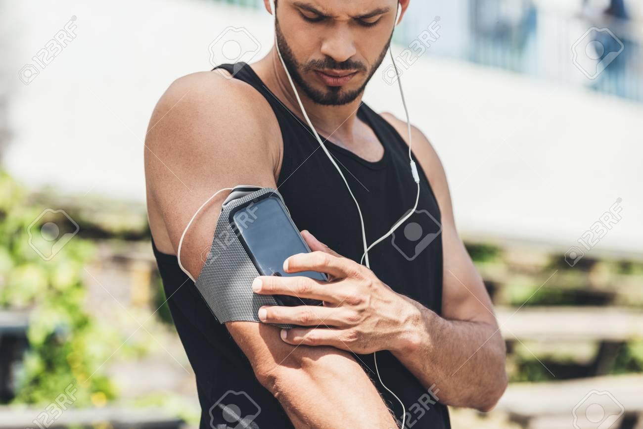 release date d082d ec113 serious young sportsman in earphones with smartphone in running..