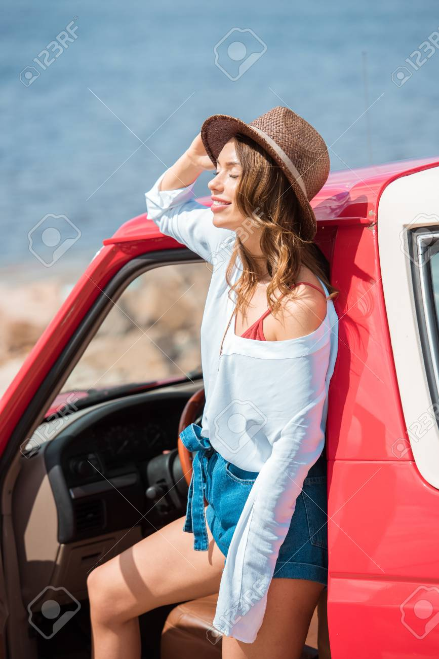 8dc84e216b737 attractive woman in hat posing at red car during road trip near the sea  Stock Photo