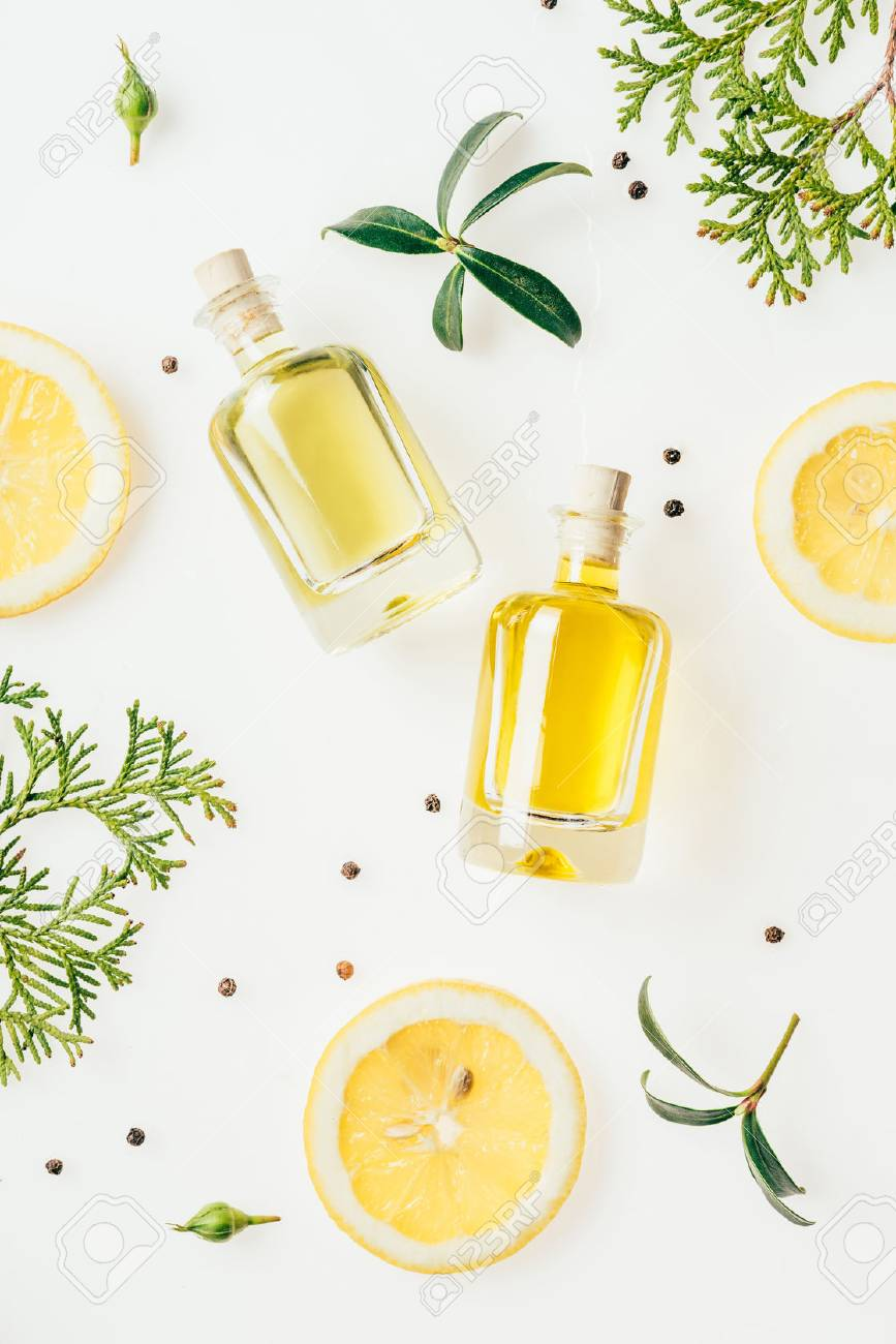 top view of bottles of fresh perfume with green branches and lemon slices on white - 106586367