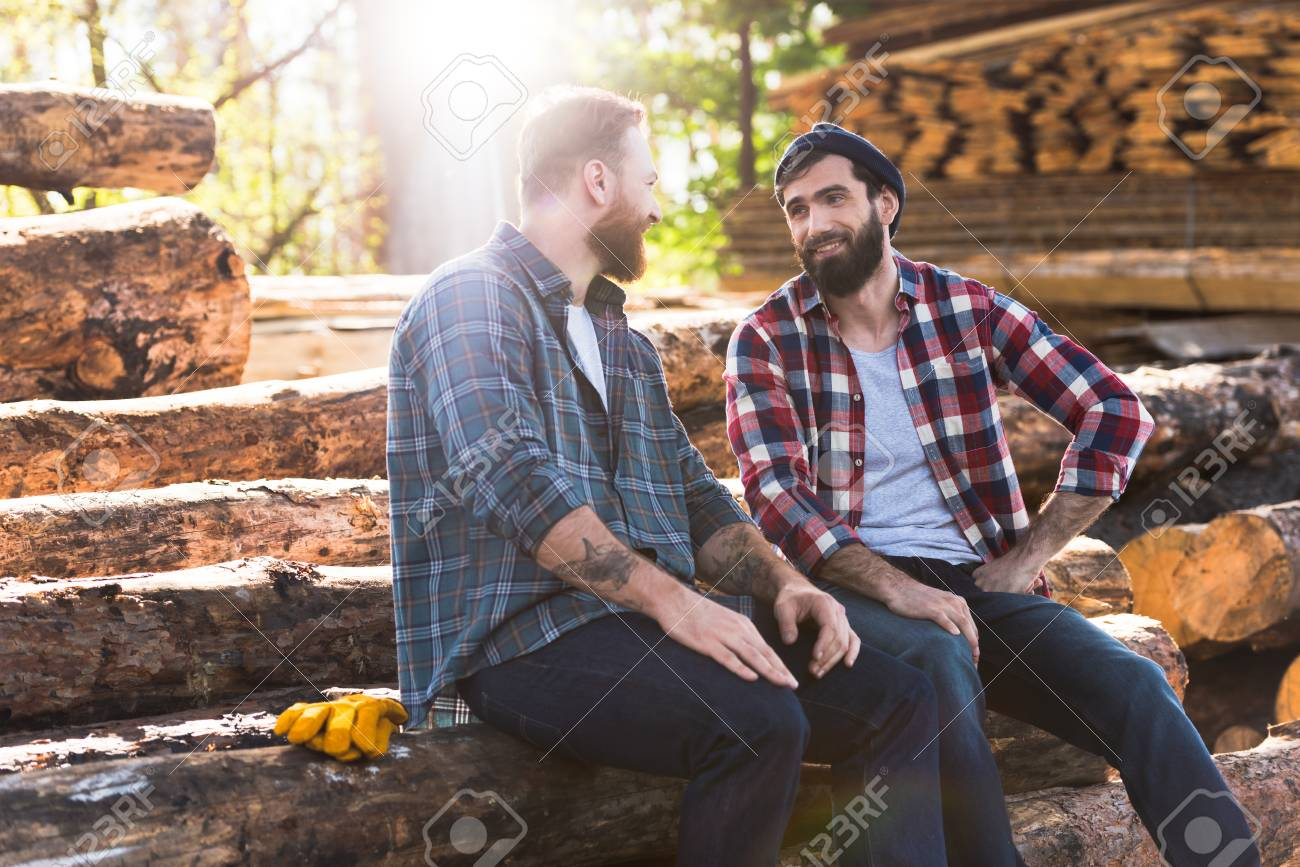 two smiling bearded lumberjacks talking to each other at sawmill - 106606048