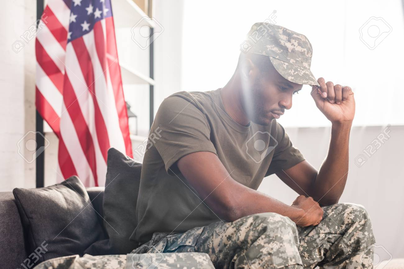 African american soldier in camouflage clothes sitting on sofa - 106750102