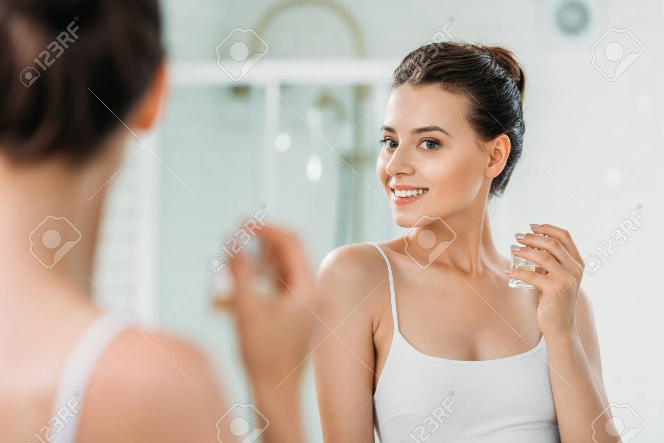 beautiful young woman holding perfume bottle and looking at mirror in bathroom - 108206838