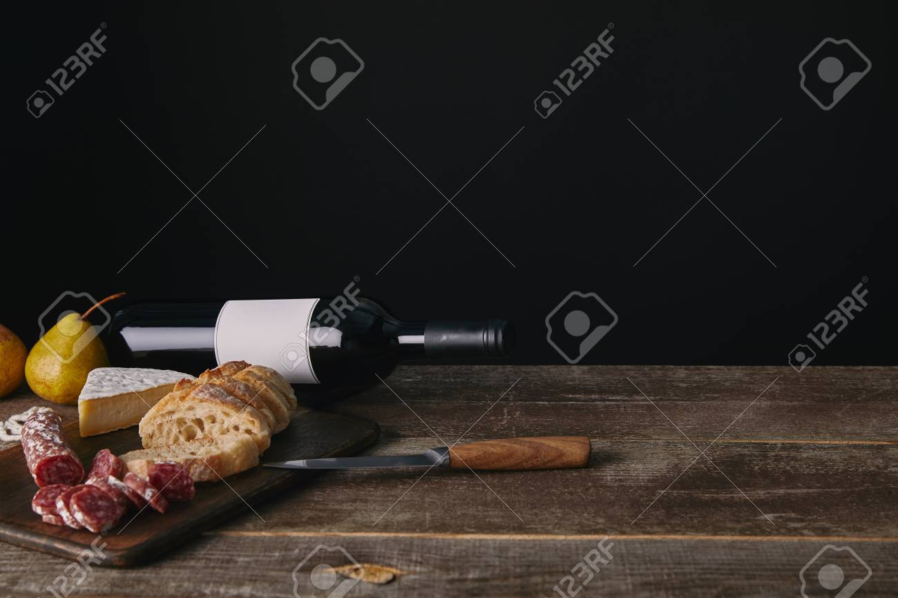 bottle of wine with blank label, pears, delicious snacks and knife on wooden table - 108723291