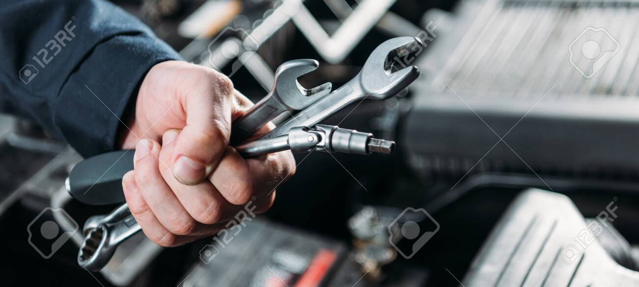 partial view of worker holding tools and wrenches in hand - 109772320