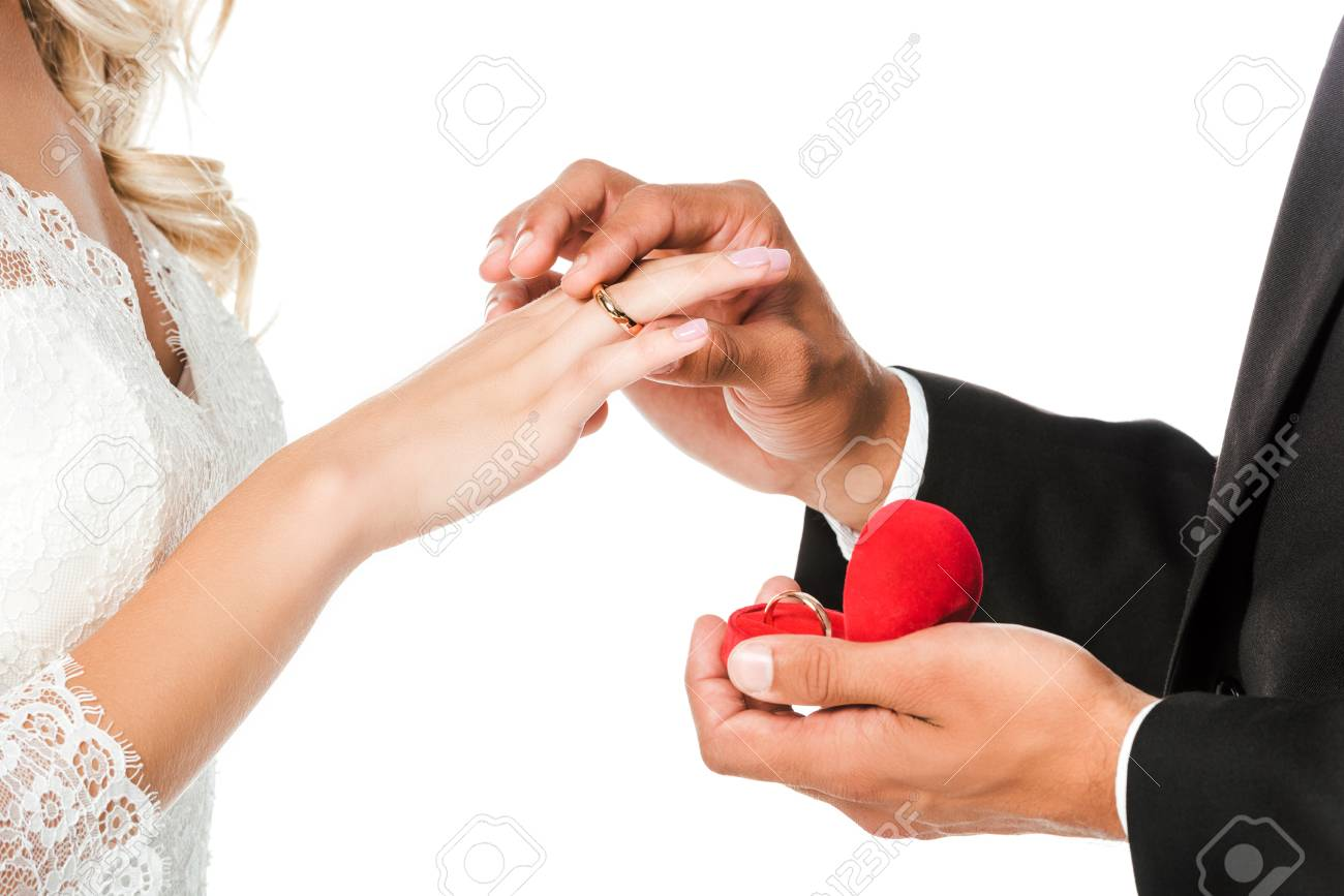 cropped shot of groom putting on wedding ring on brides finger isolated on white - 111170764
